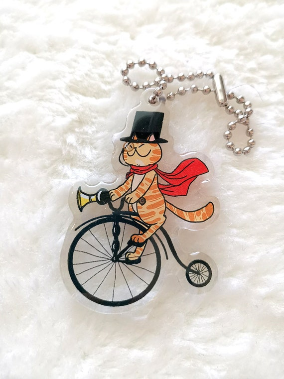 Gentleman cat riding a bike keychain charm