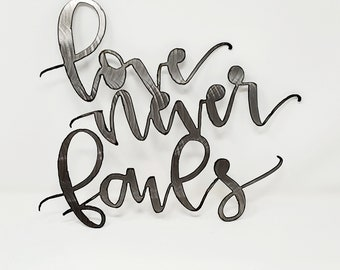 Metal LOVE NEVER FAILS spring decor hand ground using recycled materials.