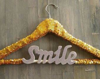 "Sequin hanger. Gold sequins with ""Smile"" script."