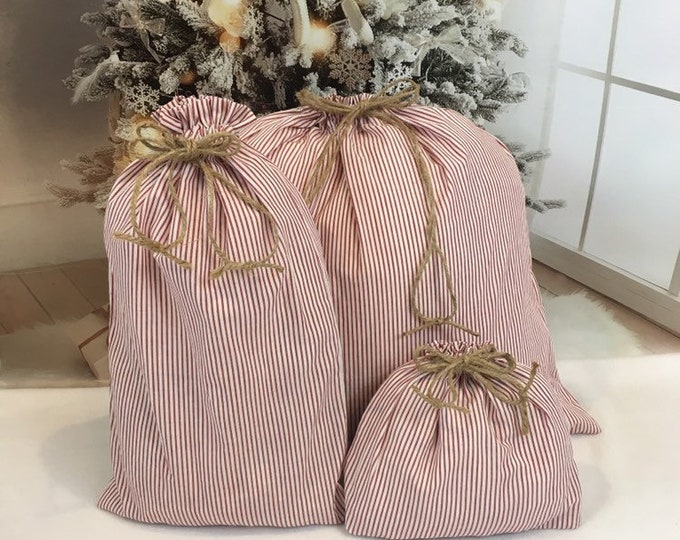 Featured listing image: Christmas fabric gift bags in farmhouse primitive muted red ticking stripe fabric, rustic rope cord drawstring, 3 sizes, reusable gift bags