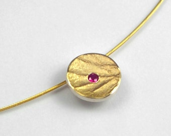 Romantic gold silver rough surfaced pendant with a genuine ruby.