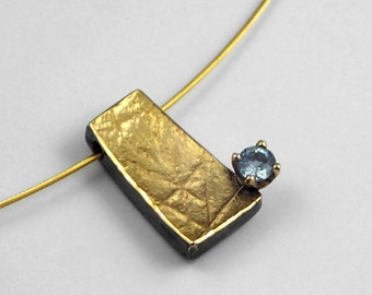 Tasteful gold silver pendant with aquamarine, oxidized silver, rough gold surface.
