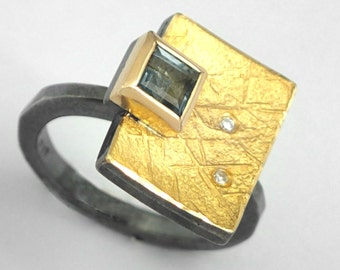 A golden book with a lock, An alternative geometric ring with a square aquamarine gemstone and small diamonds, textured ring, Artisan ring.