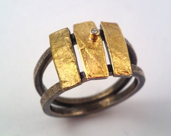 A wooden rope bridge. An alternative hammered, gold and oxidized silver ring with a diamond and a rough surface.
