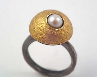 A crater of the moon. An alternative version of the geometric ring fused with 22K gold decorated with a 5.5mm pearl.