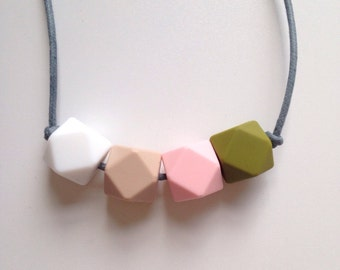 Teething necklace in white, oatmeal, pale pink and khaki green; made from BPA free chewable silicone hexagon beads by Little Gnashers