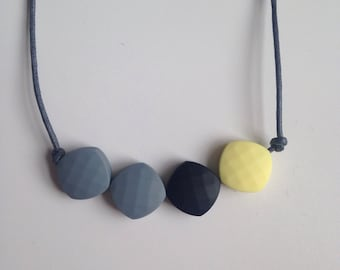 Teething necklace in pale yellow, black and grey, made from BPA free chewable silicone quadrate beads by Little Gnashers
