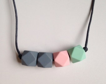 Teething necklace in grey, pale pink and mint green, made from BPA free chewable silicone hexagon beads by Little Gnashers