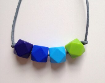 Teething necklace in navy, ultramarine, sky blue, chartreuse green; made from BPA free chewable silicone hexagon beads by Little Gnashers