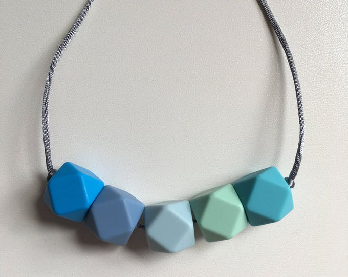 Teething necklace in sky blue, powder blue, ice blue, mint, azure; made from BPA free chewable silicone hexagon beads by Little Gnashers