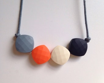 Teething necklace in grey, orange, latte and black; made from BPA free chewable silicone quadrate beads by Little Gnashers