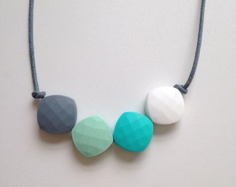 Teething necklace in grey, mint green, turquoise, white, made from BPA free chewable silicone quadrate beads by Little Gnashers