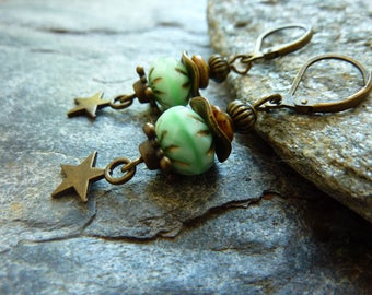 Earrings dangling bronze, and Pacific green faceted glass beads and star.