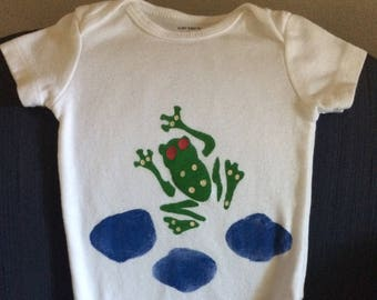 Frog Onesie with small blue puddles behind him