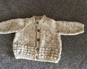 Neutral yarn, hand knitted baby sweater. Size 2
