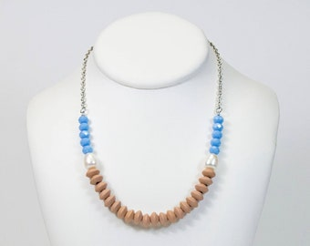 Short necklace mounted on stainless steel in wooden rings, freshwater pearls and light blue glass beads. Jewelry in pearls