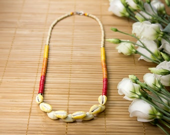 Half-long yellow shells necklace from Polynesia and vinyl from Ghana. Yellow cauris heishis necklace. Yellow-red striped necklace. Cauris Jewelry