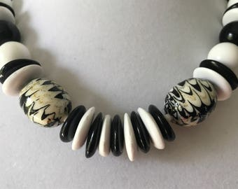 """signed Arthur David 18.5"""" black and white plastic bead necklace with two black, white and gold glitter swirls beads"""