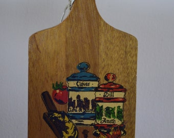 Vintage painted paddle cutting board, two canisters, vegetables, and scoop, wall hanging