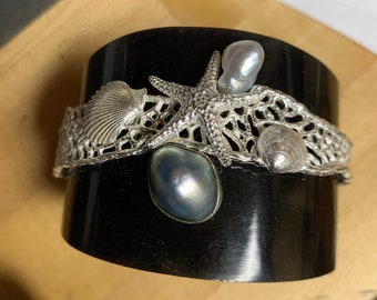 Horn cuff with sterling seafan, starfish and shells and cultured pearls.
