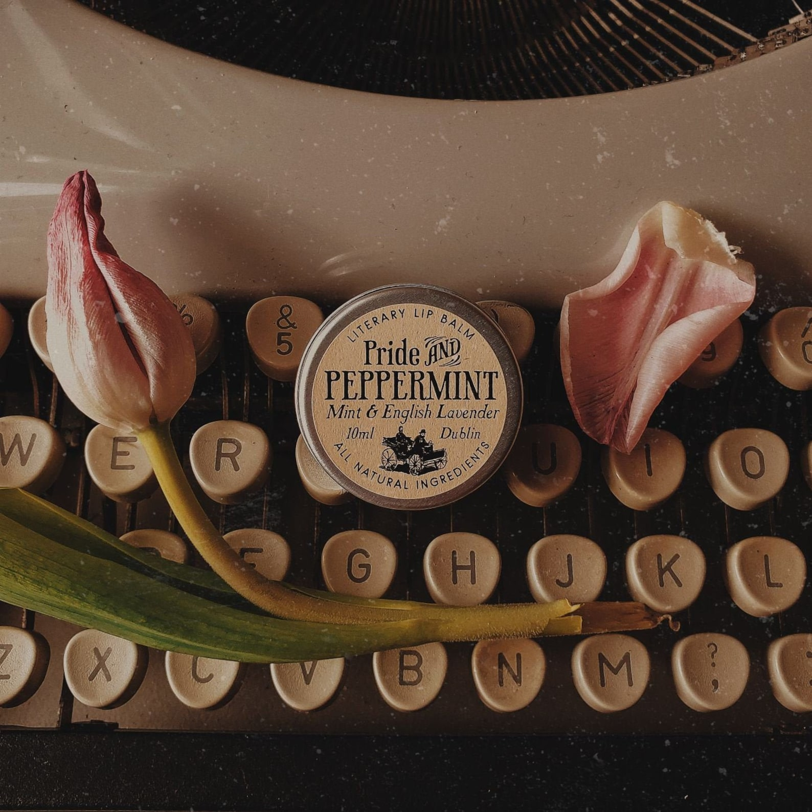 Pride and peppermint lip balm on top of older style typewriter with flower petals