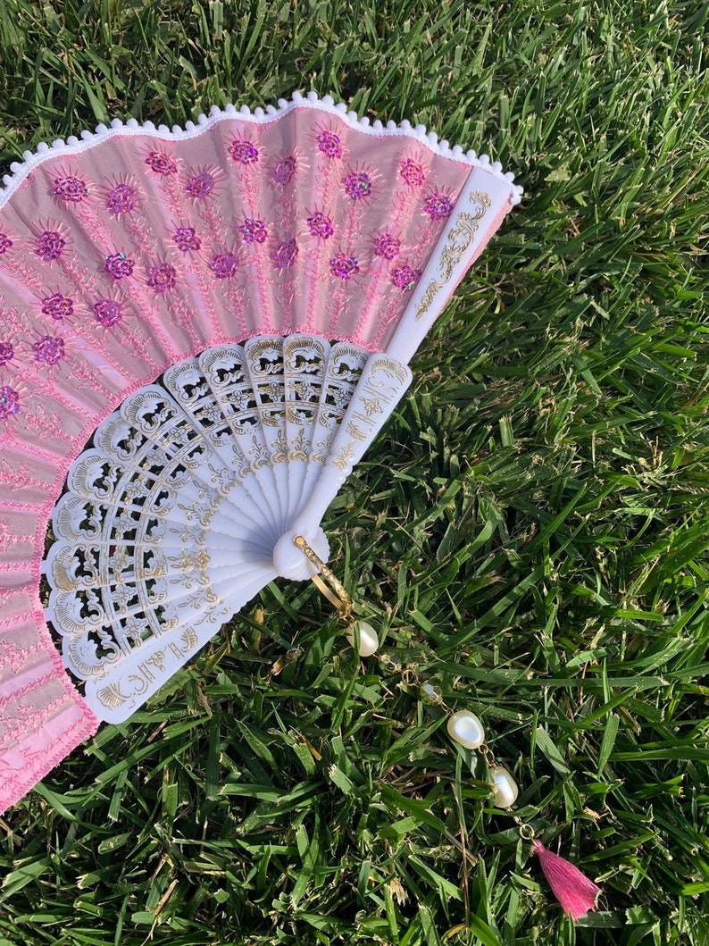Pink Handheld Fan with Pink Sequins and White Pom Pom Trim; Embellished with a rhinestone beaded charm MARIE