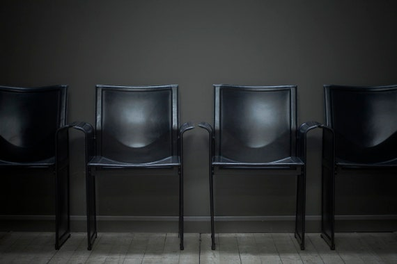 A set of four original black leather dining chairs by Tito Agnoli for Matteo Grassi