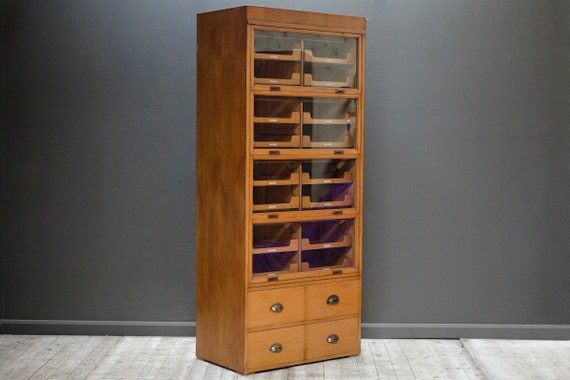 An oak glass fronted haberdashery cabinet - 16 trays and 4 drawers.