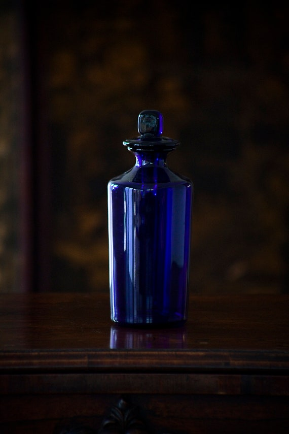 A vintage apothecary pharmacy blue glass bottle, early 1900s.
