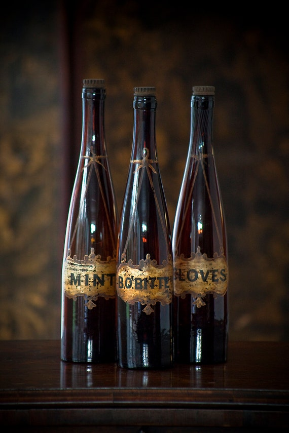 Set of three antique glass bottles from 1800s with hand-painted gilt labels