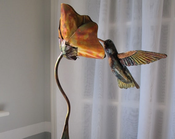 Flame painted copper sculpture on a granite base. Colorful hummingbird nectaring on a mistic flower. Aerial mistic art.