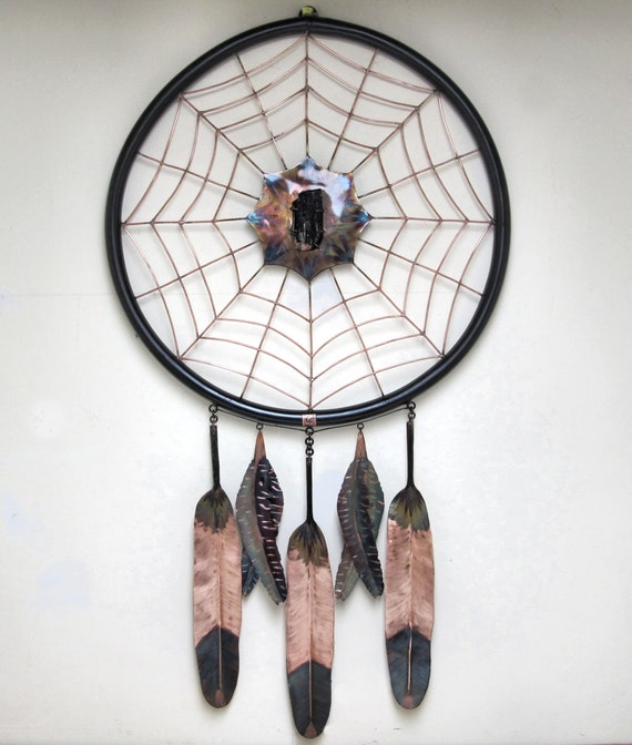Giant sculpture of a copper dream catcher. The copper is torch-colored and has received several layers of copper protection.