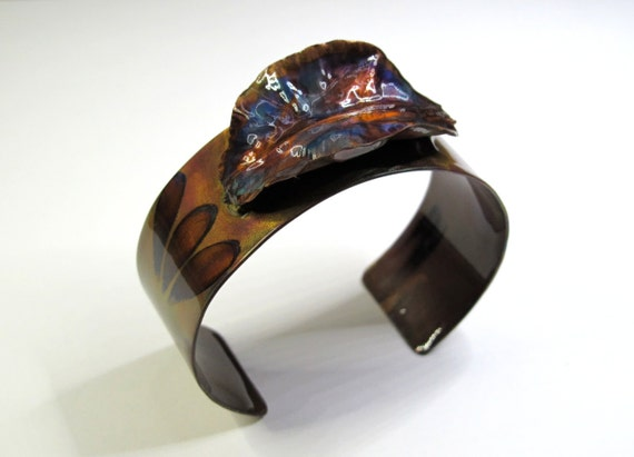 Copper Bracelet and fold forming texturized leaf. The cuff is flame painted with a torch and covered by a protective coat