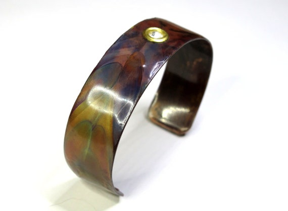 flame painted copper bracelet  with Swarovski crystal inserted. The cuff is flame painted with a torch and covered by a protective coat