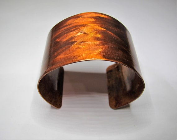 Copper Bracelet that was textured and flame painted . The cuff is covered by a protective coat