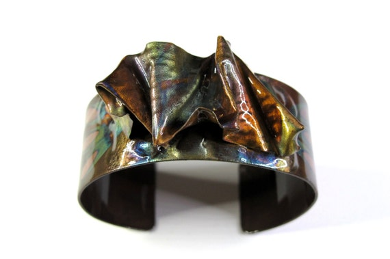 Copper Bracelet was hammered and texturized, free style. The cuff is flame painted with a torch and covered by a protective coat