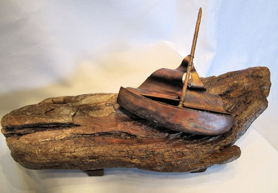 This sailboat sculpture is composed of  flame painting copper sails and a driftwood hull. The support is in wood.