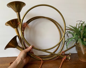 Vintage brass French horn on wood stand decor piece