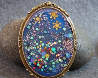 Resin brooch with snowflakes and bright glitter.