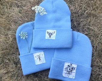 Light blue beanies with cute hand printed patches, bee beanie, watch cap, acrylic watch cap, moth beanie, flower beanie, nature punk hat