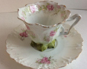 Antique demitasse cup and saucer. Delicate pink roses and green leaves demitasse cup and saucer with gold trim.