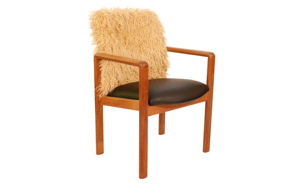 Mid-Century curated danish teak armchair with Mongolian faux fur light brown shade and vinyl black on the seat. Sturdy & Heavy.