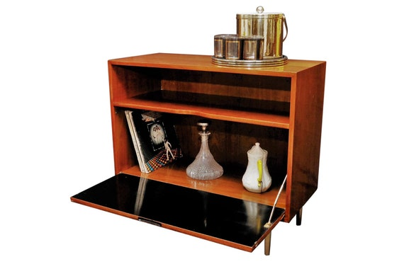 Curated mid century bar cabinet with brass legs.