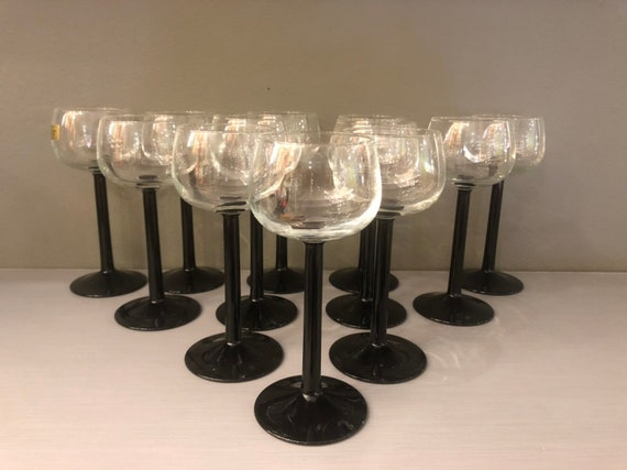 mid century set of 12 small wine glasses with a black base.