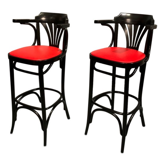 Curated Mid century wood black bar stools with red vinyl seats.