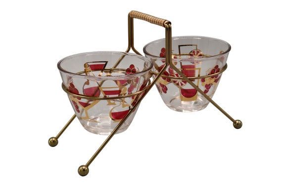 A pair of Midcentury glass serving bowls set in an atomic brass caddy.