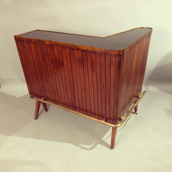 mid century mahogany L-shaped bar having brass foot rest and raised on angular legs circa 1960.