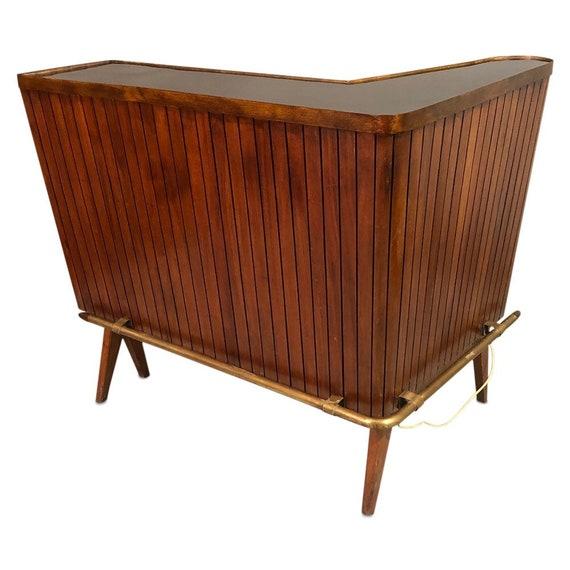 mid century mahogany L-shaped bar having brass foot rest and raised on angular legs circa 1960.