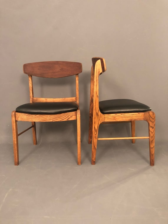 Pair of mid century walnut dining chairs with new black vinyl upholstery.