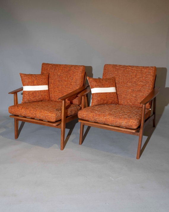 Mid century curated pair danish lounge chairs with new orange cushions. 1960's Circa